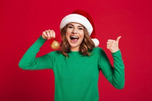 Photo of cheerful young woman wearing christmas santa hat standing isolated over burgundy background looking camera holding christmas tree toys decorations showing thumbs up.